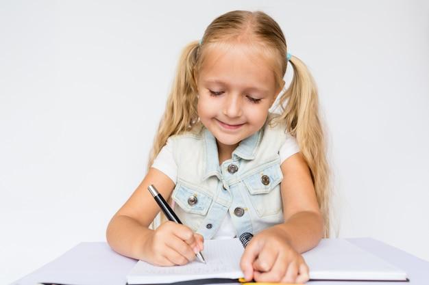 A criança bonito faz trabalhos de casa no fundo branco.