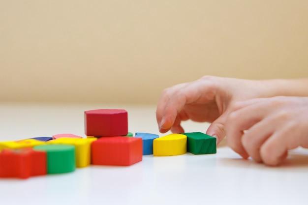 A criança brinca com figuras coloridas. detalhes do brinquedo nas mãos.
