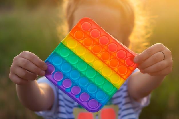 A criança brinca com um colorido jogo de poppit do arco-íris. close-up de silicone fidget.