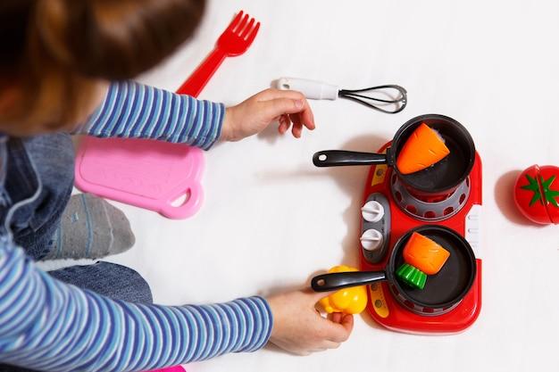 A criança brinca com vegetais fatiados de plástico e frutas com velcro, cozinha em um fogão de brinquedo em uma tigela. cozinha infantil, uma menina aprende a cozinhar. fundo branco, close-up, conceito.
