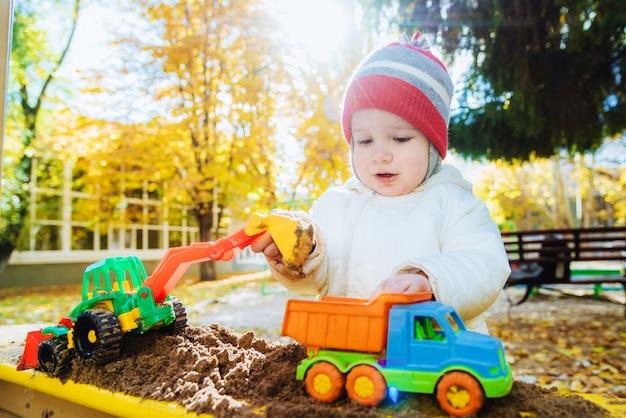 A criança brinca de carros no playground