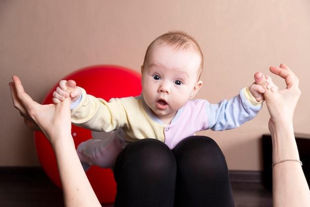 A criança brinca, faz exercícios, faz ginástica com a mãe em casa.