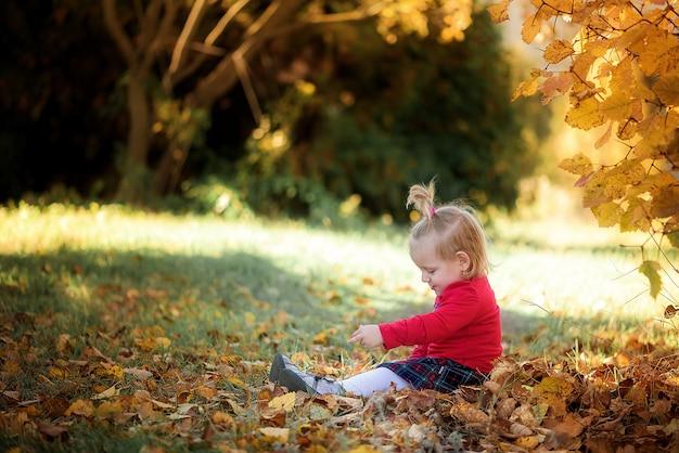 A criança brinca na floresta de outono com maçãs e lápis. tema de outono