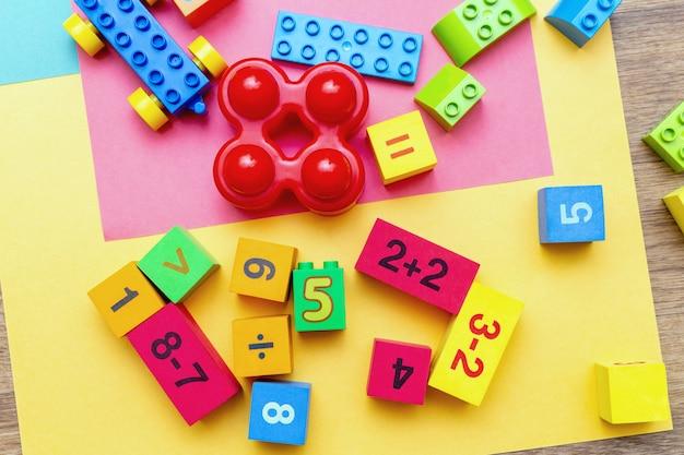A criança caçoa cubos coloridos dos brinquedos da educação com fundo do teste padrão da matemática dos números no fundo brilhante. postura plana.