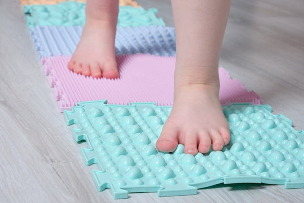 A criança caminha no colchonete para massagem dos pés em casa