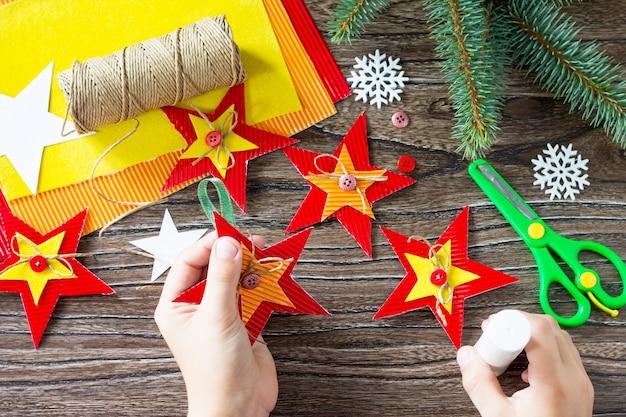 A criança cola as peças da árvore de natal, brinquedos estrela, presente. artesanato para crianças