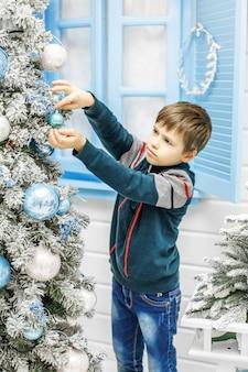 A criança colocando enfeites na árvore de natal