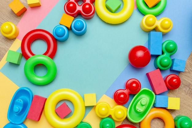 A criança colorida caçoa o teste padrão dos brinquedos da educação no colorido com espaço da cópia.