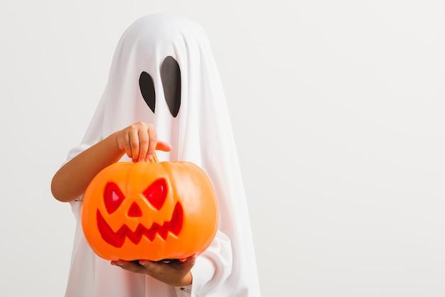 A criança com fantasia vestida de branco fantasma de halloween assustador, ele segurando o fantasma de abóbora laranja na mão