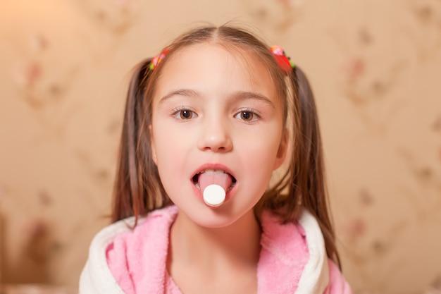 A criança com um comprimido na língua.