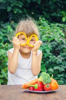 A criança come legumes no verão. foco seletivo. pessoas.