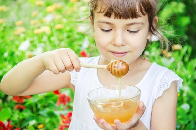 A criança come mel. foco seletivo. alimento da natureza