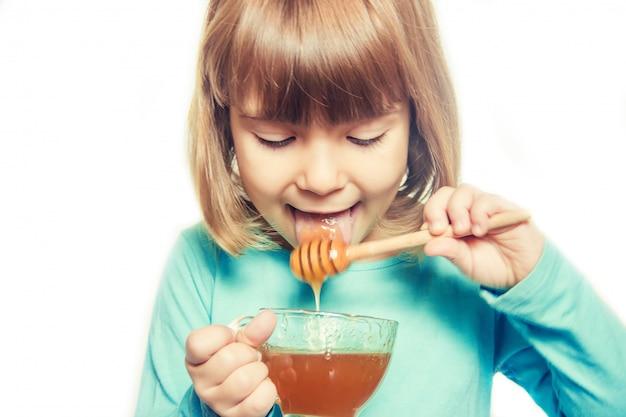A criança come mel. foco seletivo. natureza
