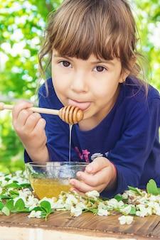A criança come mel. foco seletivo. natureza.