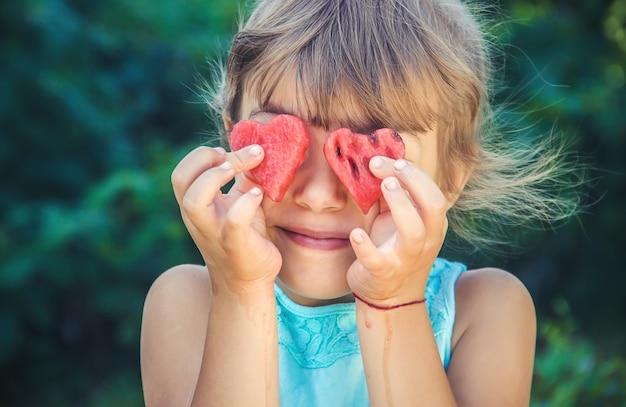 A criança come melancia no verão. foco seletivo.