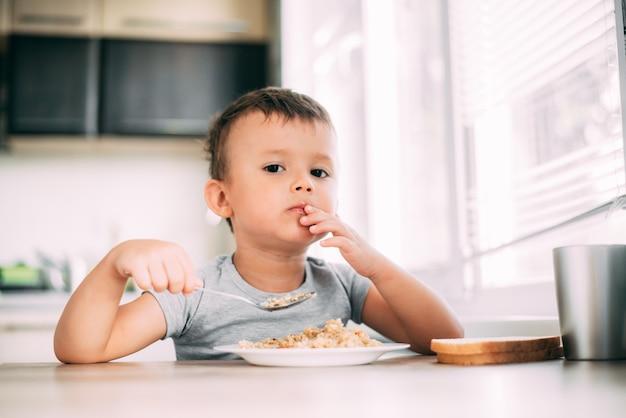 A criança come pilaf com cenoura na cozinha à tarde, muito gostoso