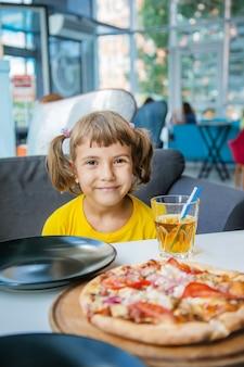 A criança come pizza de queijo.