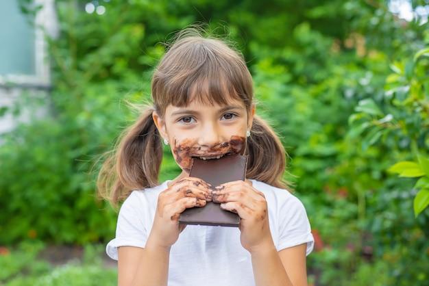A criança come uma barra de chocolate.