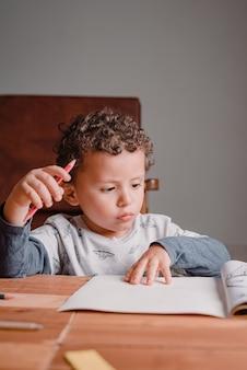 A criança concentrou-se nos desenhos de seu livro em um dia de estudos em casa