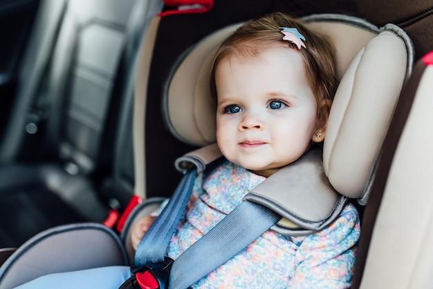 A criança consideravelmente pequena, menina com olhos azuis senta-se na poltrona do automóvel, prendida por cintos de segurança.
