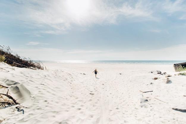 A criança corre ao longo da praia de areia branca ao longo do mar báltico.