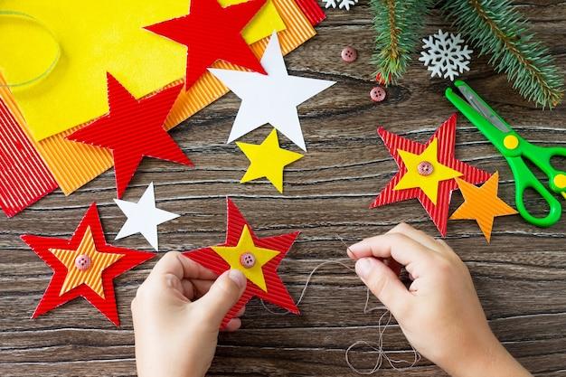 A criança costura as peças da árvore de natal, brinquedos estrela, presente. artesanato para crianças