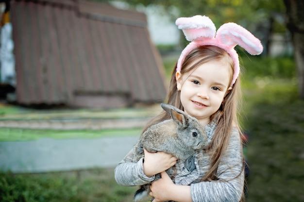 A criança de riso no ovo da páscoa caça com o coelho branco do animal de estimação.