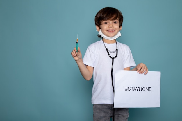 A criança de sorriso do menino pouco exploração adorável bonito fica em casa hashtag contra covid no azul