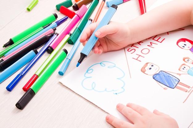 A criança desenha com canetas hidrográficas uma família e uma casa no papel