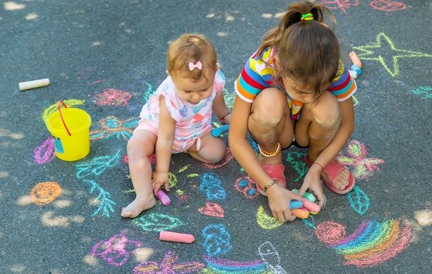 A criança desenha com giz no asfalto