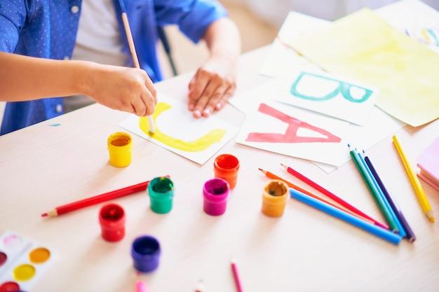 A criança desenha com um pincel aquarela pinta no papel a letra c