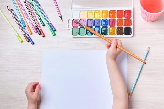 A criança desenha com um pincel no papel