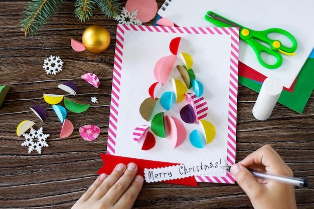 A criança desenha detalhes cartão de saudação da árvore de natal artesanato feito à mão para crianças