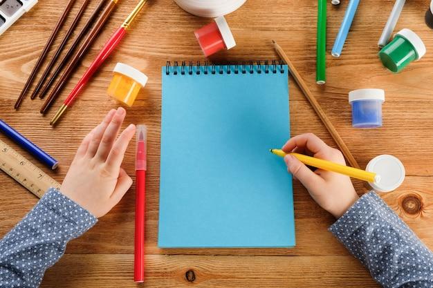 A criança desenha em um caderno com canetas e tintas de feltro.