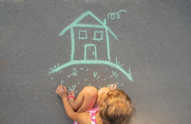 A criança desenha uma casa de giz. foco seletivo.
