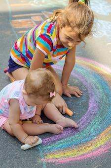 A criança desenha uma casa e um arco-íris no asfalto com giz