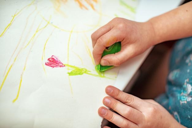A criança desenha uma flor em papel com lápis de cera feitos com as próprias mãos
