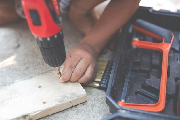 A criança do menino que guarda a mão utiliza ferramentas a chave de fenda elétrica.
