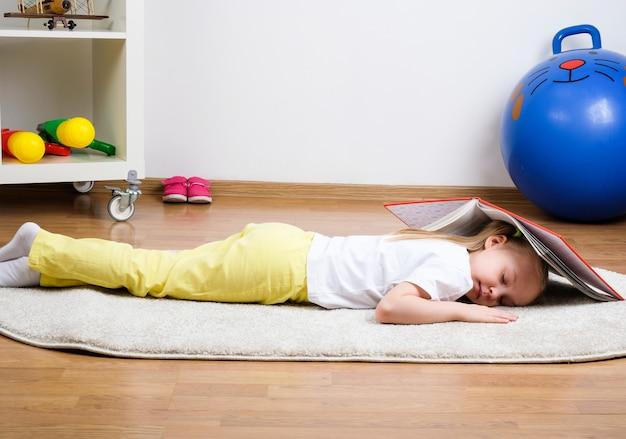 A criança dorme no chão com um livro. a menina está cansada e dormindo.