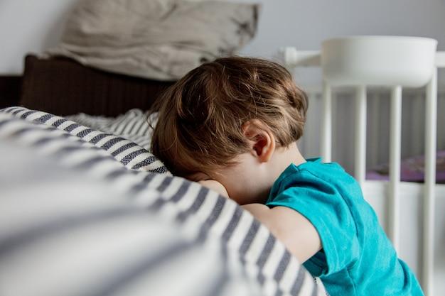 A criança dormindo colocou a cabeça em uma cama