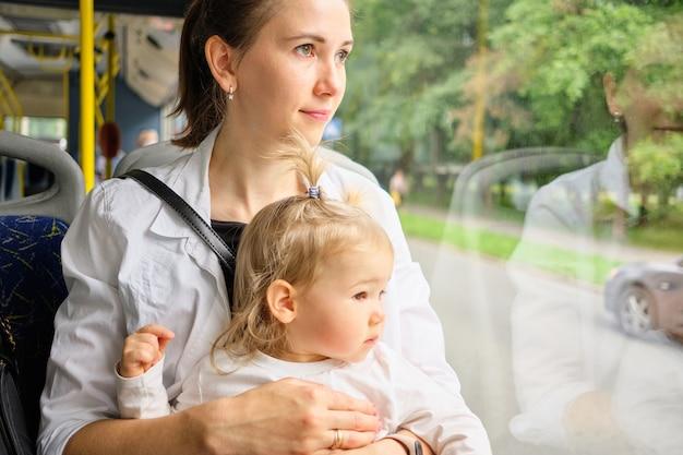A criança e a mãe sentam-se no banco do ônibus e olham pela janela