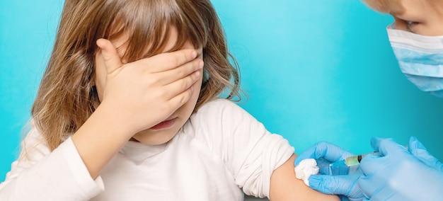 A criança é injetada no braço. foco seletivo.