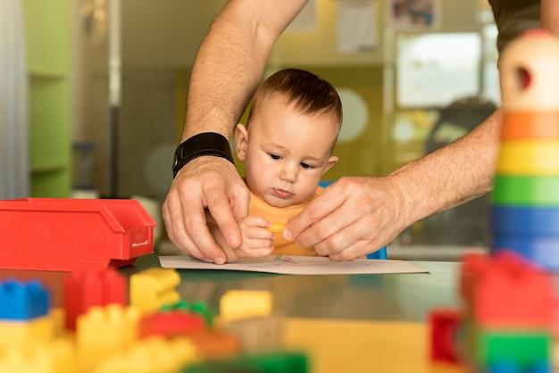 A criança e o pai estão desenhando em um papel. conceito de jardim de infância.