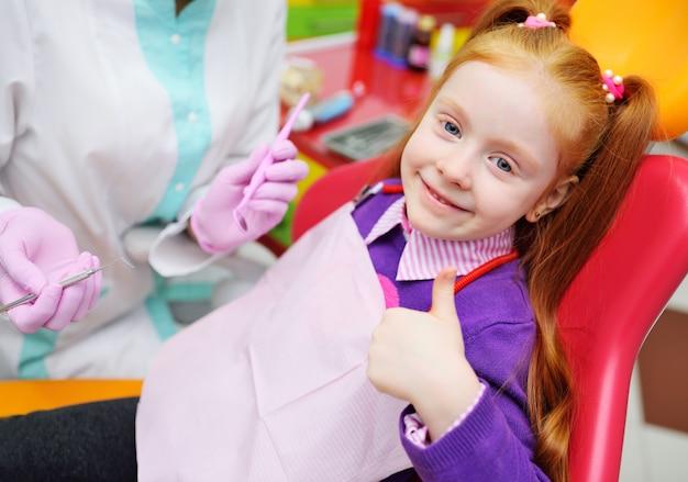 A criança é uma garotinha ruiva sorrindo sentado em uma cadeira odontológica.