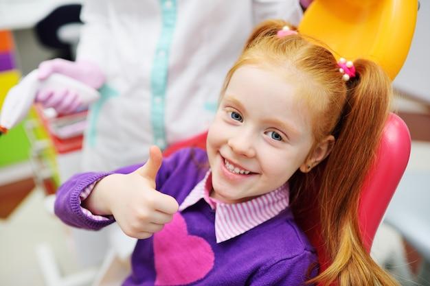 A criança é uma garotinha ruiva sorrindo, sentado em uma cadeira odontológica.
