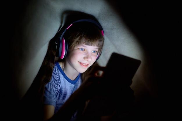 A criança em fones de ouvido sem fio ouve música à noite debaixo de um cobertor e olha para o tablet