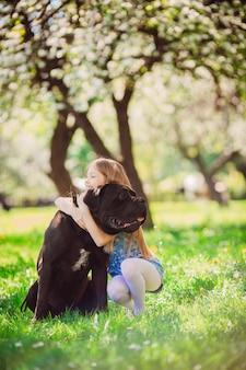 A criança encantadora abraçando um cachorro preto