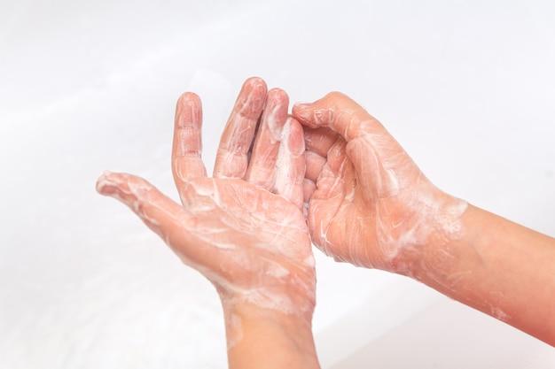 A criança ensaboa as mãos com sabonete closeup em um fundo branco