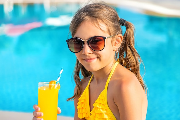 A criança está bebendo um coquetel na piscina