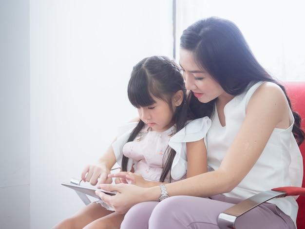 A criança está brincando na cadeira com sua mãe